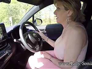 Mature chick Sonia plays with her funbags while driving